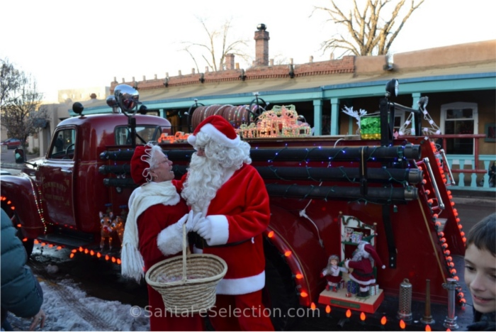 Mr & Mrs Claus beside the vintage fire truck.