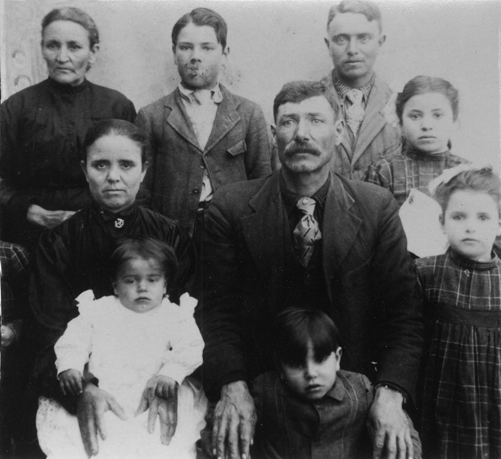 Young Ross Salazar with family. Ross is under the hands of his father.