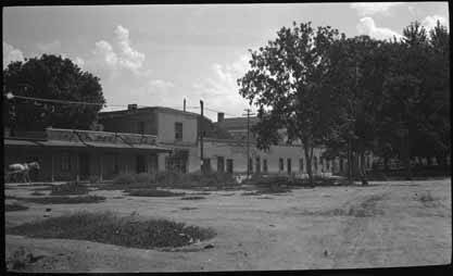 The block of Spanish Colonial buildings housing Prince Patio and Sena Plaza. Title: Prince Plaza and Sena Plaza Palace Avenur at Cathedra Place Santa Fe, NM. circa 1920-30. Photo: Palace of the Governors Photo Archive.