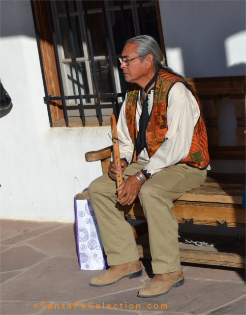 Philip Mangas Haozous watching the singers before he performs the Native flute songs he learned from his father.